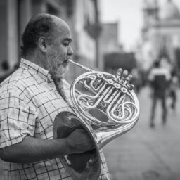 black and white photo of a man playing a french horn